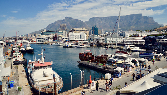 Cape Town the capital city of South Africa, busy fishing harbour beside the Victoria and Albert Waterfront. Tourists wander along boardwalk and busy fish restaurants. Cape Town, Western Cape, South Africa. November 2018