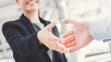 Young businesswoman going to make handshake with a businessman -greeting, dealing, merger and acquisition concepts