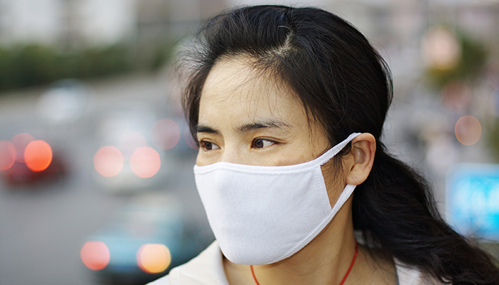 Beautiful Chinese woman wearing a white face mask against pollution or disease