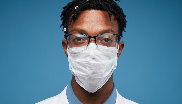 Head and shoulders portrait of young African-American doctor wearing protective mask and looking at camera while posing against blue background