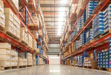 Rows of shelves with goods boxes in huge distribution warehouse at industrial storage factory.