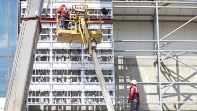 Belgrade, Serbia - May 6, 2020: Construction workers in crane basket installing external cladding metal structure on a building facade wall