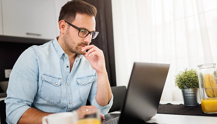 Man using laptop computer, working at home. Worried about finances.