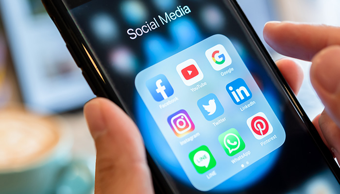 BANGKOK, THAILAND- 26 June 2019 : Hands of man use Iphone 7 plus with social media application of facebook, youtube, google search, instagram, twitter, linked in, line whatsapp, and pinterest on black background