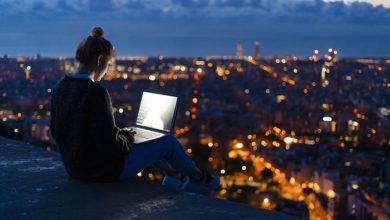 Young woman using laptop at dawn above the city, Barcelona, Spain