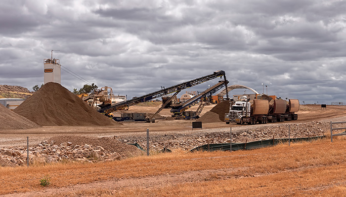Clermont, Queensland, Australia - 04/27/2020; Working quarry with machinery and gravel with a truck being filled to supply the new Adani Carmichael mine in central Queensland, Australia.