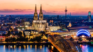 Cologne, Germany - August 2019: Beautiful panoramic aerial night landscape of the gothic catholic Cologne cathedral, Hohenzollern Bridge and the River Rhine at sunset golden hour and blue hour.