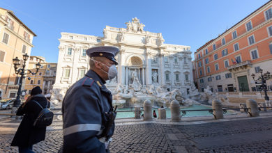 ROME, ITALY - 10 March 2020: A city Police man wearing a face mask walks across the deserted Trevi Fountain square. The Government decreed a nationwide quarantine, with travel and gatherings ban. Rome, Metropolitan City of Rome, Italy