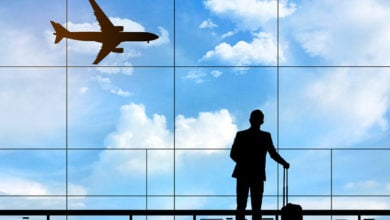 Silhouette of businessman standing at the terminal airport with airplane background, hand holding the luggage during waiting for flight boarding time, business and travelling concept.
