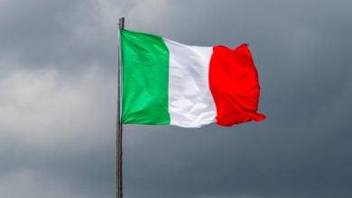 Italian flag against menacing dark storm clouds in the background