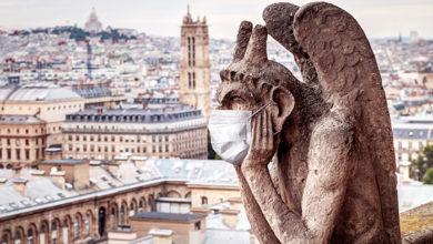 COVID-19 coronavirus in France, medical mask on gargoyle of Notre Dame de Paris. Tourist landmarks closed due to corona virus. Concept of travel in Europe, quarantine, lockdown and COVID pandemic.