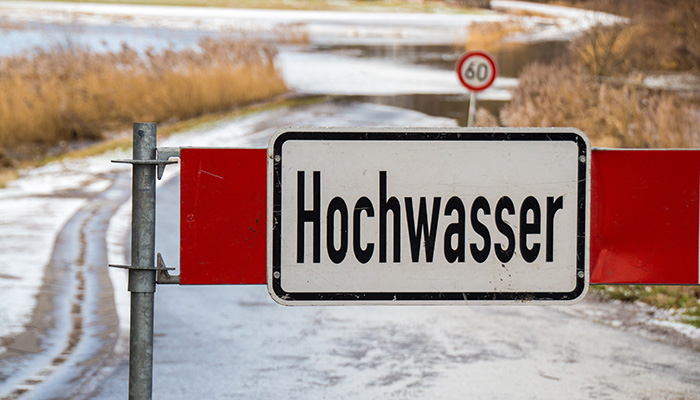 Road barrier with flood warning sign in front of flooded road in germany