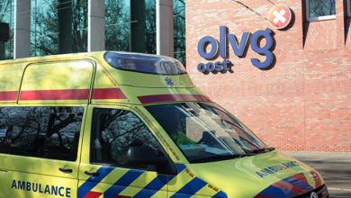 AMSTERDAM / NETHERLANDS - April 9th 2020: Ambulance rides to the hospital OLVG in Amsterdam, one of those that treat patients with covid-19. Facade and logo.