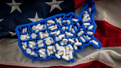Healthcare, opioid epidemic and drug abuse concept with the map of USA filled with oxycodone and hydrocodone pharmaceutical pills on the American flag