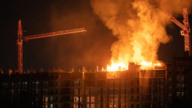 construction site in fire at night. 60 square meters of fire at the top level of a building under construction. Burning particles and big pieces of burning wood is falling down.