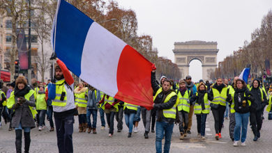 Paris / France - December 15 2018: 5th Yellow Vests demonstration (Gilets Jaunes) protesters against fuel tax, government, and French President Macron with French flag at Champs-Élysées