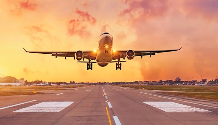 Commercial airliner passenger plane fly down over landing at sunset