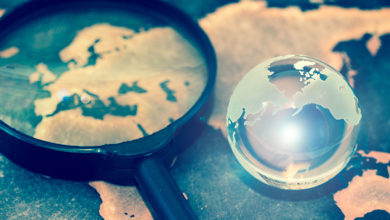Crystal globe on grunge world map, with lens flare
