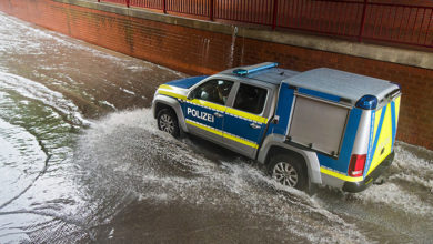 Brake, Germany - July 14, 2021: a vehicle of the water police drives through the railroad underpass flooded after a cloudburst - water splashes