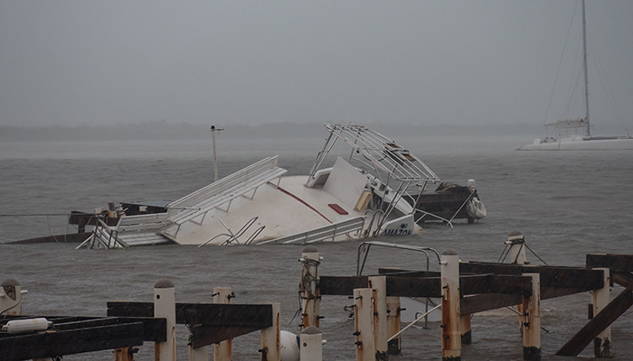 West Bay, Grand Cayman, Cayman Islands - August 18th 2021: Hurricane Grace. A shot in the rain of damage to the Cayman Islands including these boats that were sunk and the dock that was ruined.
