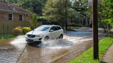 NEW ORLEANS, LA, USA - SEPTEMBER 15, 2021: Car splashes through flooded street