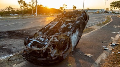 Durban, South Africa, 15 July 2021. The wreck of a destroyed car lies on a pavement, after being vandalized and set of fire during a violent protest in the area.