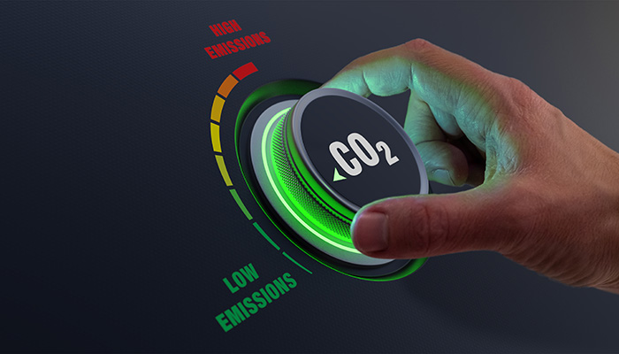 Lower CO2 emissions to limit global warming and climate change. Concept with manager hand turning knob to reduce levels of CO2. New technology to decarbonize industry, energy and transport