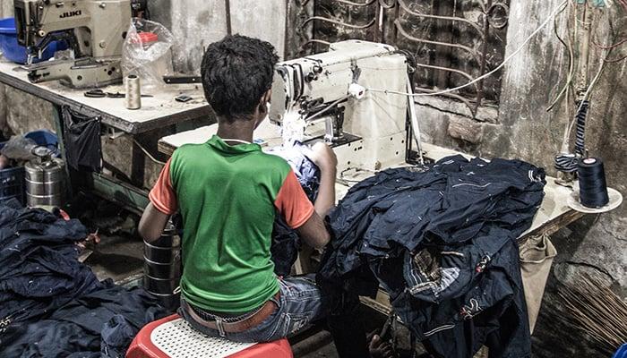 DHAKA, BANGLADESH - JANUARY 06, 2017: Child labor in a garment factory in Bangladesh